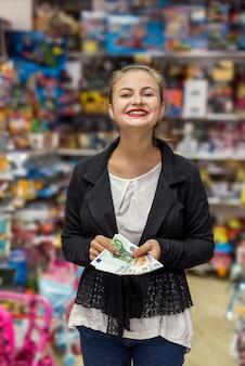 ユーロ紙幣を保持しているおもちゃ屋で幸せな女性