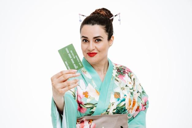 白で親指を示すクレジットカードを示す伝統的な日本の着物の幸せな女性