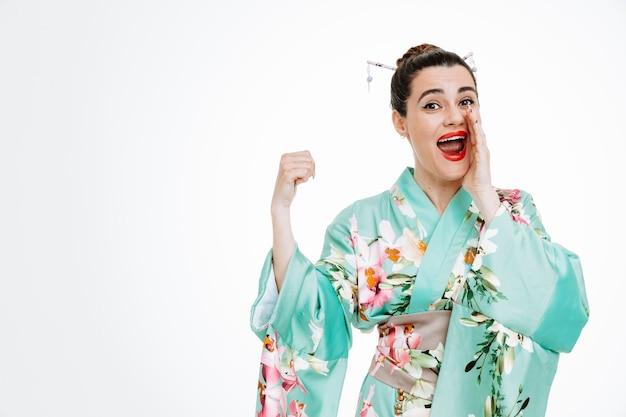 일본 전통 기모노를 입은 행복한 여성이 흰색에 놀란 쪽을 엄지손가락으로 가리키는 입에 손을 잡고 비밀을 말하고 있다