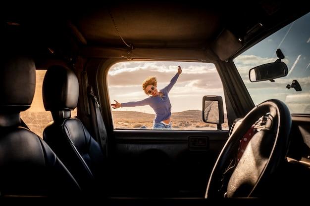 旅行の冒険ライフスタイルの夏休みの幸せな女性は、ドアを通して車の内側から見た車の外で陽気で笑顔でジャンプします-ロードトリップと女性ドライバーの概念-自由な旅の生活