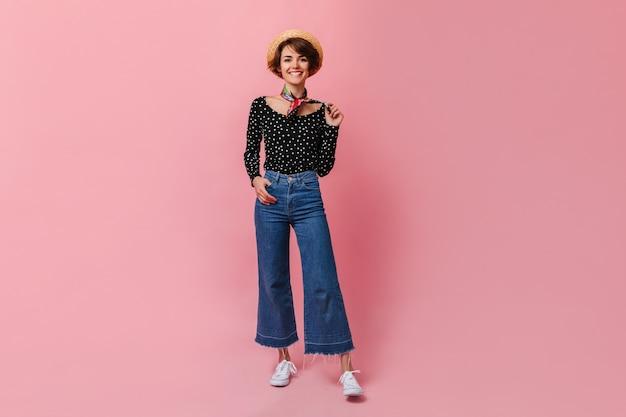 ピンクの壁に立っているヴィンテージジーンズの幸せな女性