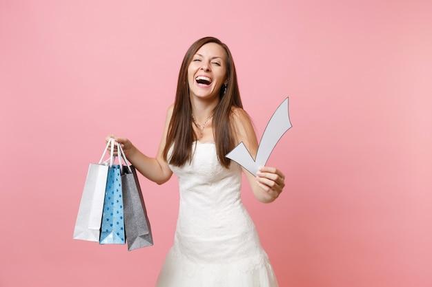 Счастливая женщина в белом платье держит галочку, разноцветные пакеты с покупками после покупок