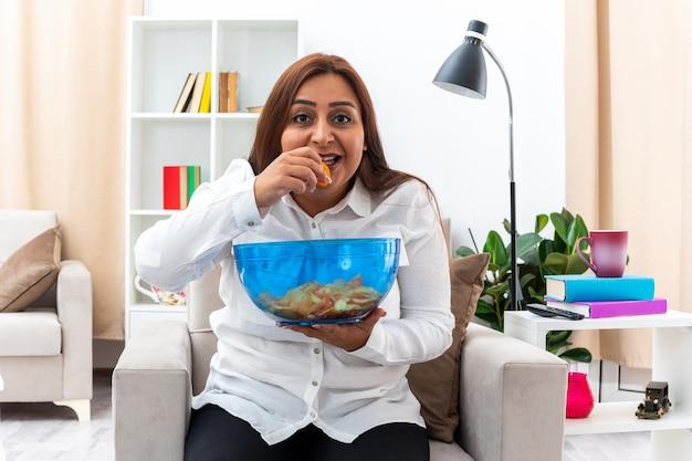 白いシャツと黒いズボンを着た幸せな女性が、明るいリビング ルームでチップを食べるチップのボウルを持って椅子に座ってリラックス