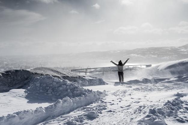 雪に覆われたフィールドを背景に冬の服を着て幸せな女性