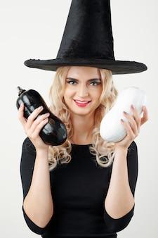 Счастливая женщина в шляпе ведьмы, показаны кабачки