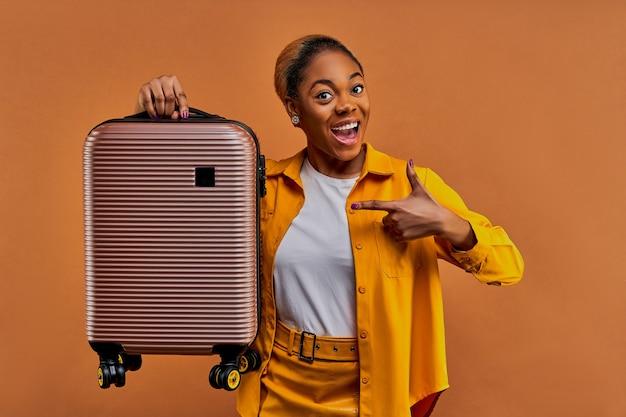 Счастливая женщина в желтом держит в руке чемодан с колесами и показывает на него пальцем. концепция путешествия