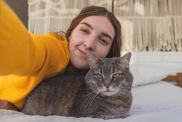 黄色いセーターを着た幸せな女性は、明るいインテリアのベッドで灰色の猫を抱きしめます