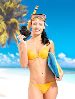 ビーチで写真を撮るデジタルカメラと黄色の水着で幸せな女性