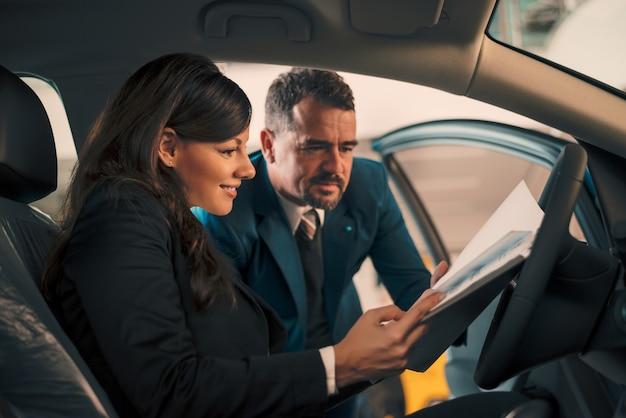 Happy woman inside car in auto salon with car dealer.