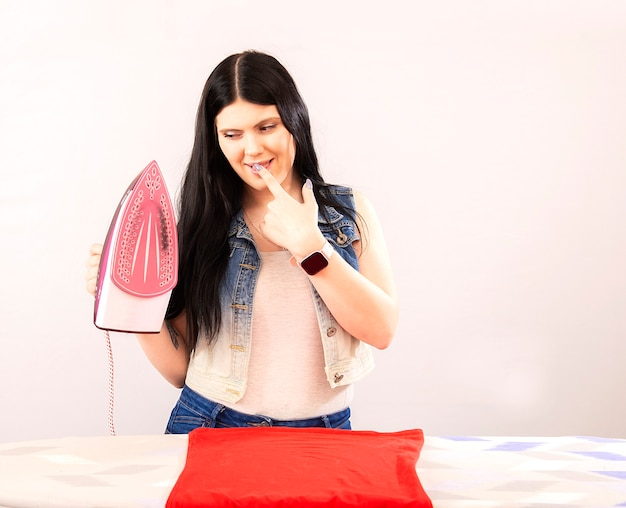 Happy woman ironing clothes with electric iron isolated