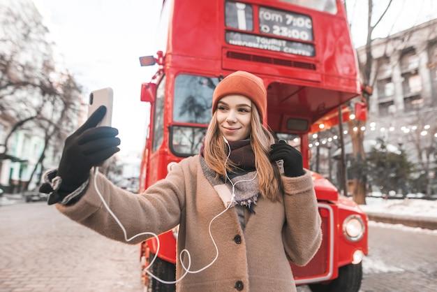 행복한 여자는 빨간 버스의 배경에 촬영 된 따뜻한 옷을 입은 관광객입니다.