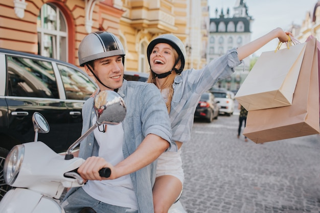 Happy woman is holding shopping bags in hand and enjoying white his boyfriend drives a motorcycle