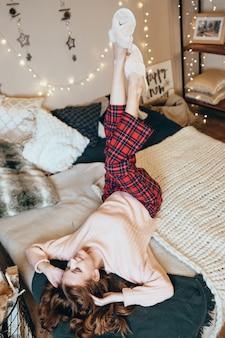幸せな女性は、クリスマスによって美しく装飾された明るく居心地の良い寝室にいます