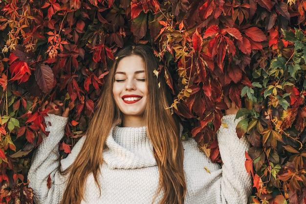 Счастливая женщина лежит на стене из красных листьев плюща.