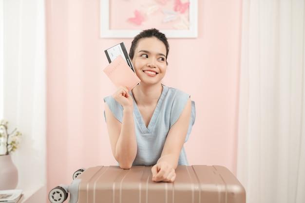 幸せな女性はスーツケースが近くに立っている間、パスポートとチケットを手に自宅でスーツケースを梱包しています