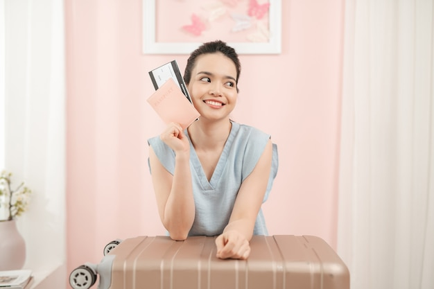 Happy woman is packing suitcase at home with passport and ticket in hand while suitcase is standing nearby
