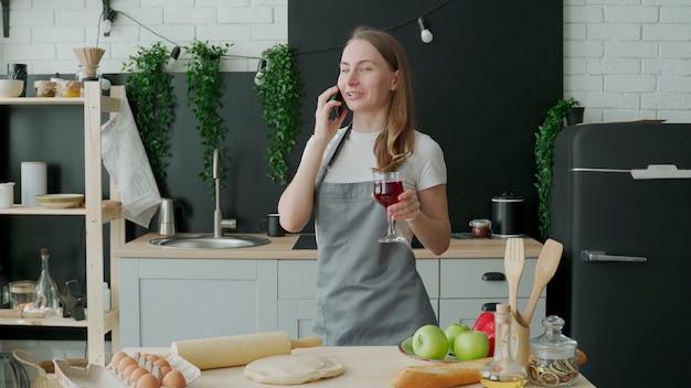 幸せな女性は彼女の携帯電話で話し、彼女の台所でワインを飲んでいます