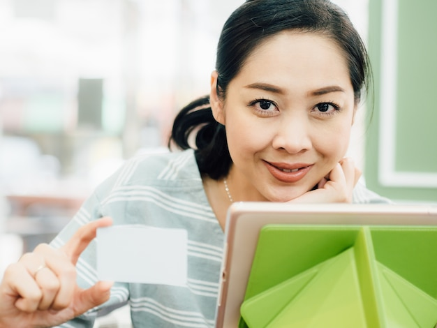 Happy woman is using a white mockup credit card for online shopping on tablet