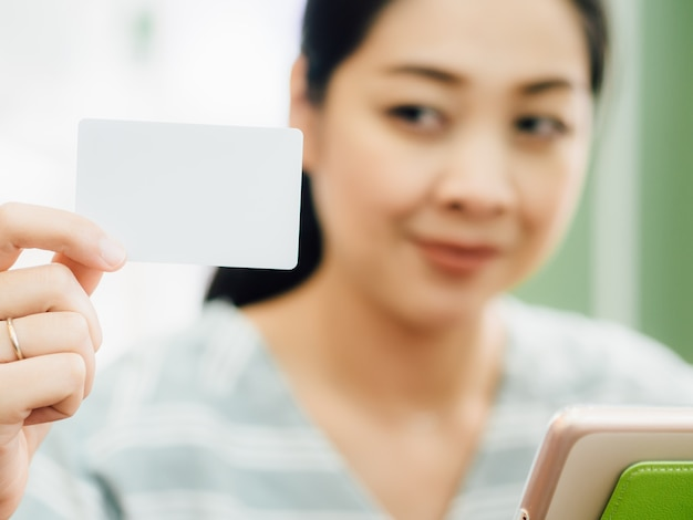 Happy woman is using a white mockup credit card for online shopping on tablet.