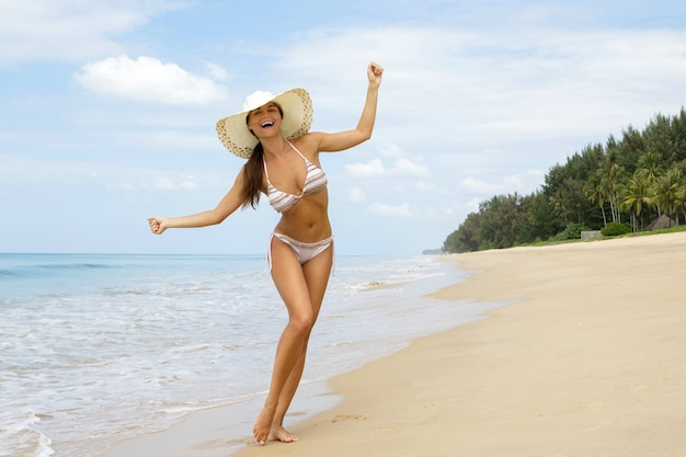 Happy woman is walking on the sea coast