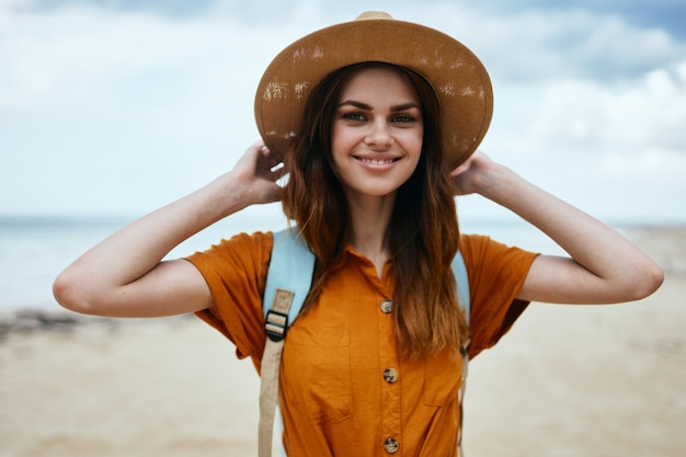 Happy woman on the island with a hat on her head and a backpack
