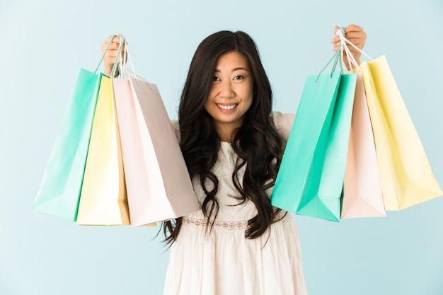 쇼핑백을 들고 파란색 벽에 고립 된 행복 한 여자