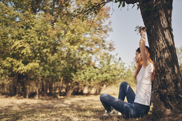 Happy woman in jeans in a t-shirt sits near a tree with her hands up