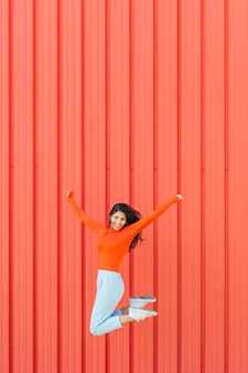 Happy woman jumping against red corrugated background while arm outstretched