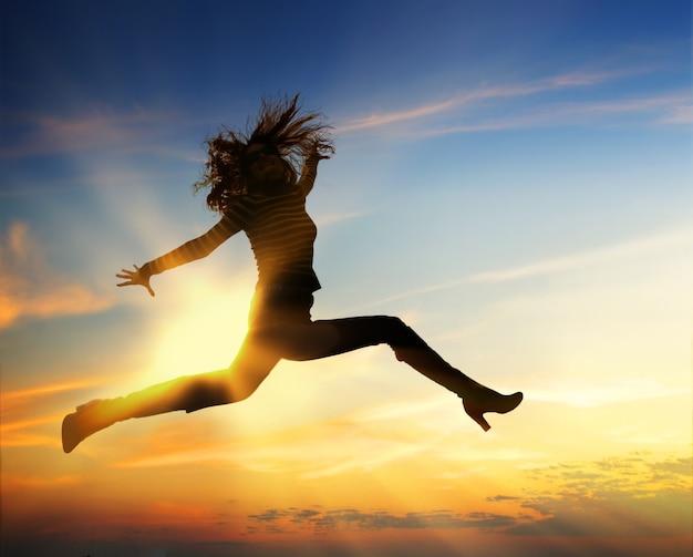 푸른 흐린 하늘에서 점프 하는 행복 한 여자