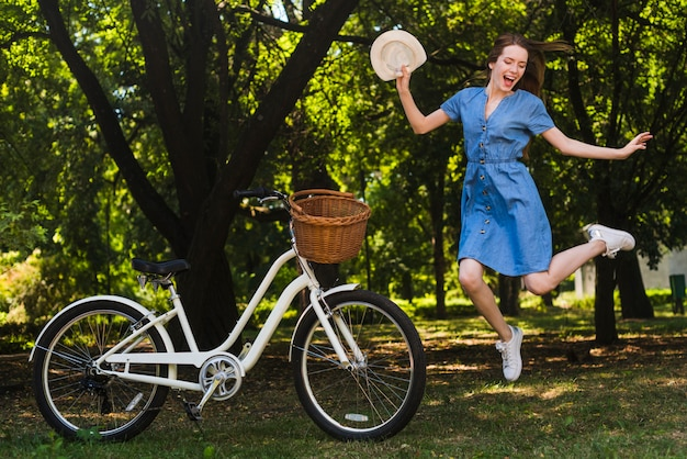 Happy woman jumping next to bike