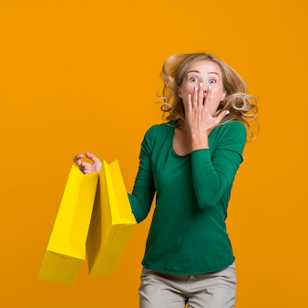 Happy woman jumping while holding many shopping bags