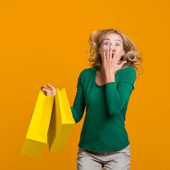 Счастливая женщина прыгает, держа в руках много сумок
