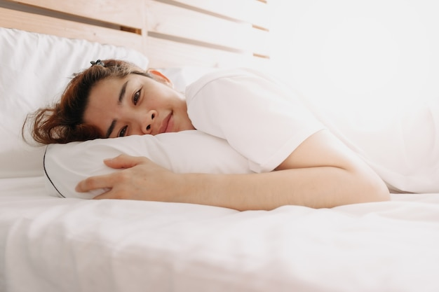 Happy woman just wake up on her bed in warm summer morning