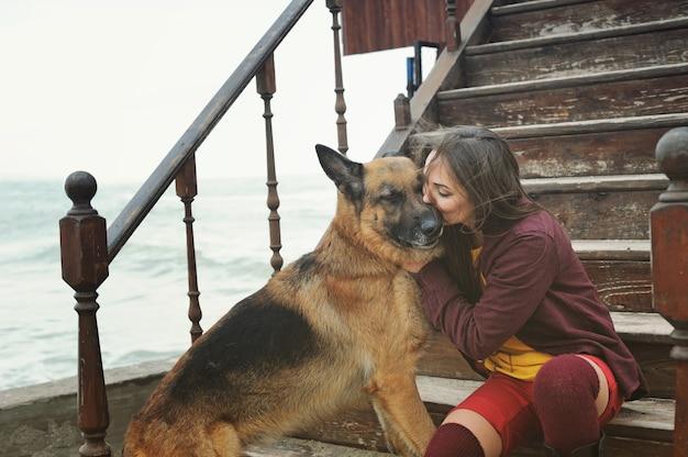 彼女のジャーマンシェパード犬にキスする幸せな女性