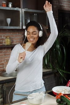 Happy woman in kitchen singing