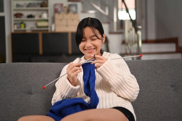 소파에 파란색 스웨터를 뜨개질 하는 행복 한 여자.