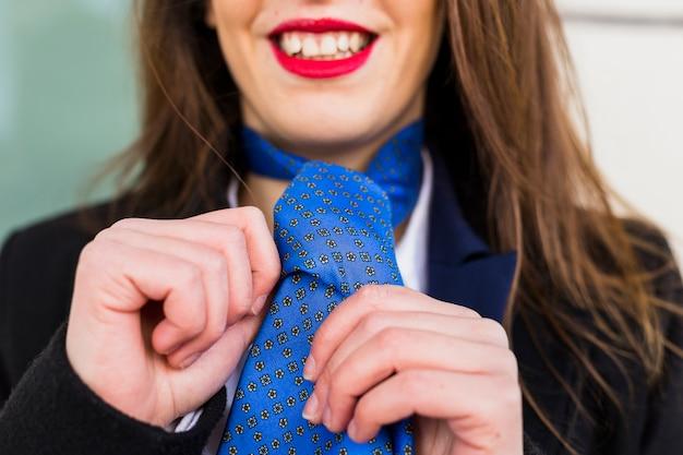 Happy woman knotting blue tie