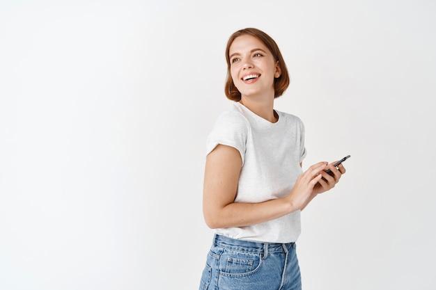 웃으면서 휴대 전화를 들고 옆으로 찾고 행복 한 여자. 스마트폰, 흰 벽에 채팅하는 동안 웃고 응시하는 귀여운 소녀