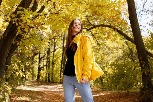 가을 노란 잎 앞에서 노란 옷을 입고 웃고 있는 행복한 여자. 미소 가을