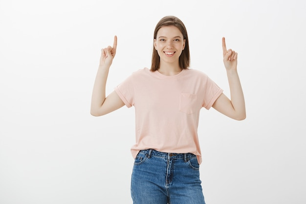 Happy woman laughing and smiling, pointing fingers up at your logo, banner promo