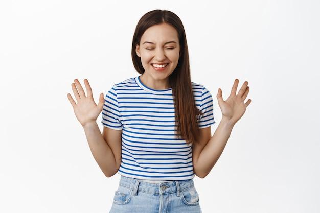 Счастливая женщина смеется, улыбается белыми зубами, поднимает пустые руки, стоит веселая и взволнованная, в полосатой летней футболке и джинсах, белая стена