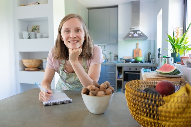 Happy woman leaning on counter with fruits and nuts in kitchen, writing notes in notebook and looking at camera. cooking at home concept