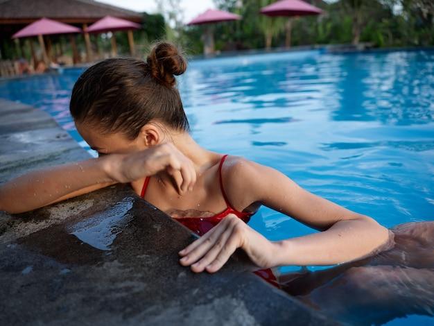 プールのタイルに寄りかかって、モデルの手の肖像画で彼女の顔を覆う幸せな女性