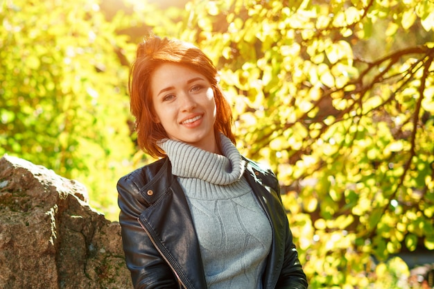 Happy woman in a leather jacket in a park near a tree smiling