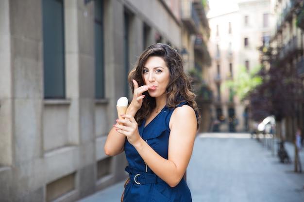 Donna felice leccare il dito mentre mangia il gelato