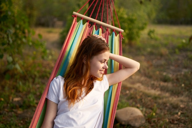 Happy woman lies in a hammock outdoors in the forest laughing. high quality photo
