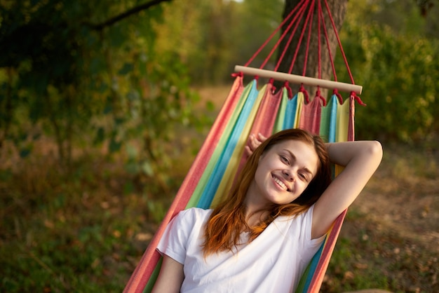 Happy woman lies in a hammock outdoors in the forest laughing smile model. high quality photo Premium Photo