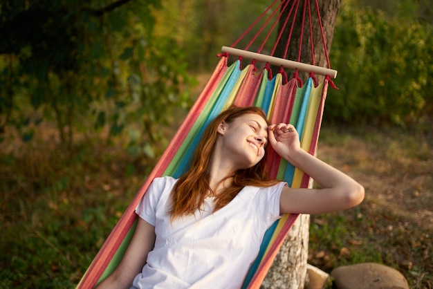 Happy woman lies in a hammock outdoors in the forest laughing Premium Photo