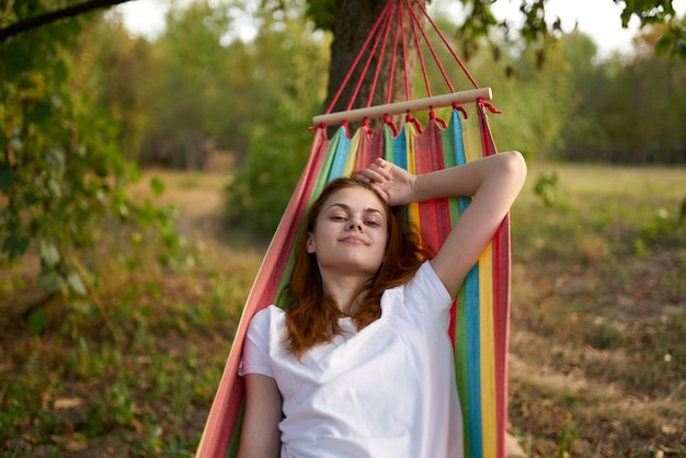 Happy woman lies in a hammock outdoors in the forest laughing