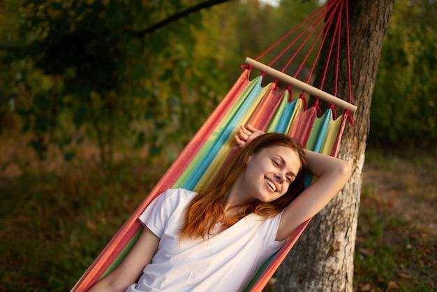 幸せな女性は、笑顔のモデルを笑っている森の屋外のハンモックに横たわっています。